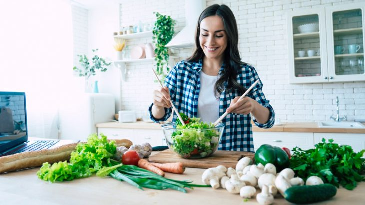 Young woman preparing vegetable salad