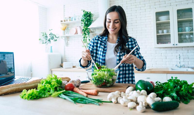 Young woman preparing vegetable salad